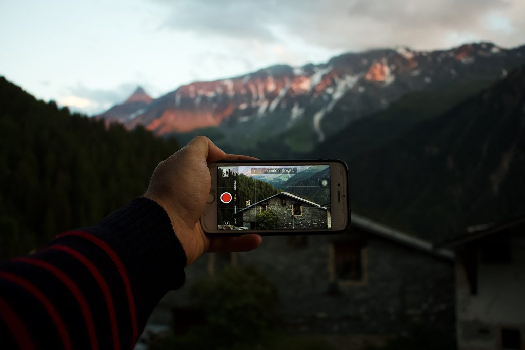 A guy shooting footage of a mountain using his smartphone