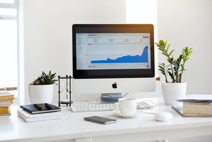 Displaying the Google Analytics stats on a desktop screen at a white desk